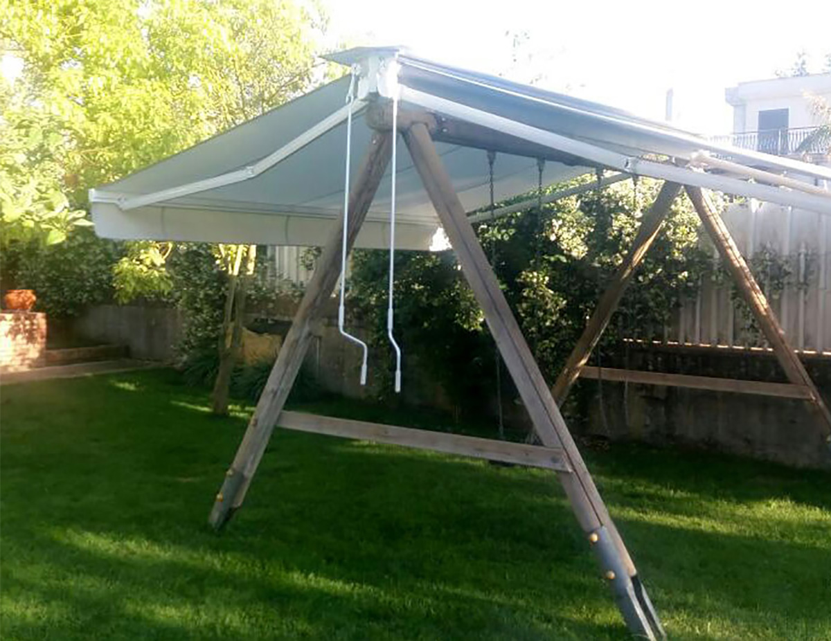 Altalena in legno utilizzata all'occorrenza come gazebo sfruttando la base superiore come appoggio per due tende a bracci con tessuto tempotest parà.