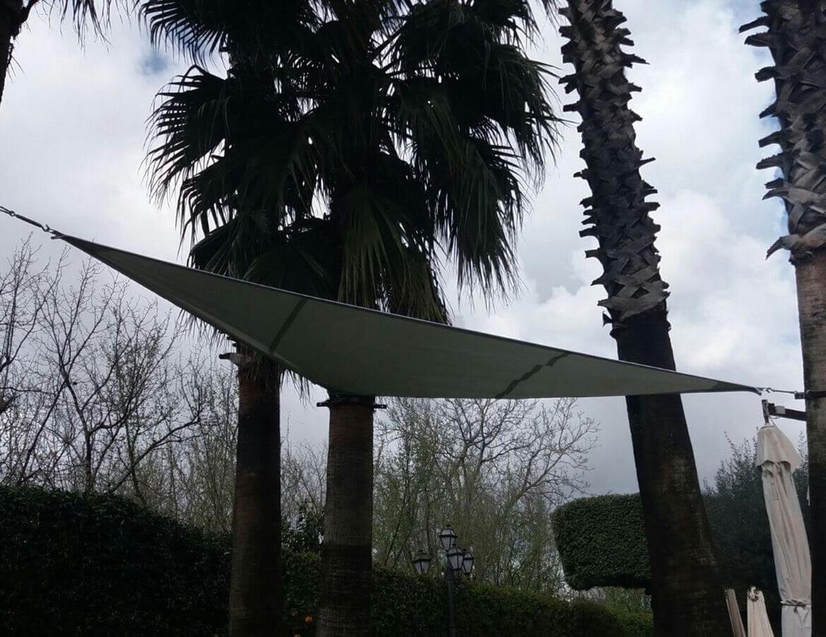 Gazebo a vela senza piantoni legato alle tre estremità a fusti di albero